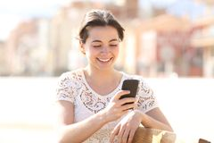 Happy lady uses a smartphone in a park stock photo