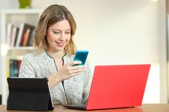 Happy lady using multiple colorful devices. On a desk at home royalty free stock photos