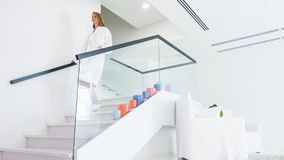 Happy lady walking down staircase at spa stock footage