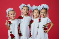 Happy large family of four sisters in embroidered white dresses on a plain red background in the studio royalty free stock photography