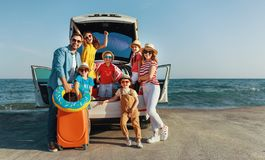 Happy large family  in summer auto journey travel by car on beach stock photography