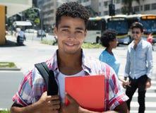 Happy latin american male student in cityq Stock Photos