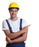 Happy latin construction worker pointing sideways Stock Photos