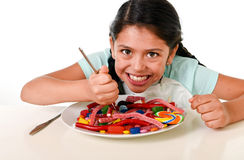 Happy Latin female child eating dish full of candy and gummies with fork and knife and big cola bottle in sugar abuse. Happy hispanic female child eating dish Stock Photo