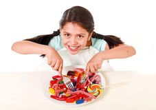 Happy Latin female child eating dish full of candy and gummies with fork and knife and big cola bottle in sugar abuse. Happy hispanic female child eating dish Royalty Free Stock Image