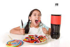 Happy Latin female child eating dish full of candy and gummies with fork and knife and big cola bottle in sugar abuse Stock Photos
