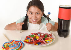 Happy Latin female child eating dish full of candy and gummies with fork and knife and big cola bottle in sugar abuse. And sweet nutrition excess isolated on Royalty Free Stock Photography