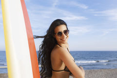 Happy Latin female relaxing after surfing on the ocean during her recreation time Royalty Free Stock Image