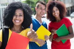 Happy latin female student with curly black hair and friends Stock Photos
