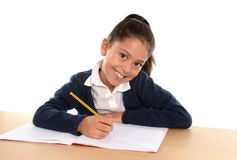 Happy latin little girl with notepad smiling in back to school and education concept. Happy sweet little hispanic female child writing homework with pencil Royalty Free Stock Photo