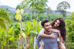 Happy Latin Man Carry Woman On Back, Young Couple Over Green Tropical Rain Forest Landscape Stock Images