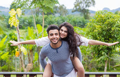 Happy Latin Man Carry Woman On Back, Young Couple Over Green Tropical Rain Forest Landscape Royalty Free Stock Images