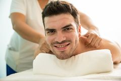 Happy Latin man getting a massage royalty free stock photos