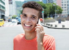 Happy latin man at phone in city Royalty Free Stock Photography