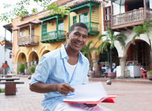 Happy latin student in a colonial town with paperwork. Happy latin student with paperwork with buildings of a historic colonial town, street and traffic people Stock Images