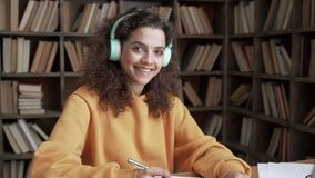 Happy latin teen girl student wear headphone look at camera learn online laptop.