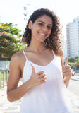 Happy latin woman in the city showing thumb up Stock Photo