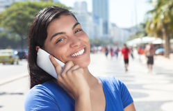 Happy latin woman with long dark hair at phone in city Stock Image
