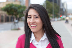 Happy latin woman with a pink vest outside in the city Stock Photography