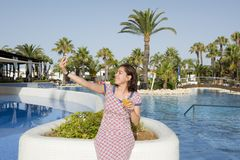 Happy latin woman taking selfie while on holidays. Happy attractive latin woman smiling while taking a selfie with a pool in the background while on holidays at Stock Image