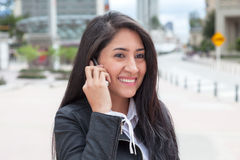 Happy latin woman talking at phone in the city Royalty Free Stock Photos