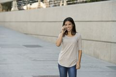 Happy latin woman on urban street city background talking on mobile phone with a sweet smile Royalty Free Stock Photos