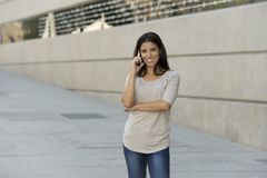 Happy latin woman on urban street city background talking on mobile phone with a sweet smile Stock Photo