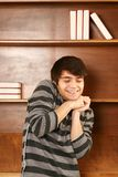 Happy latino-asian man in front of book shelf Stock Photos