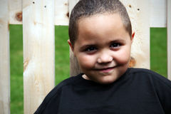Happy latino boy. Leaning against fence Stock Images