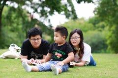 Happy latino family reading book Stock Photos