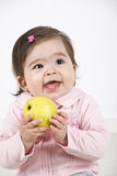 Happy laughing baby with apple Stock Images