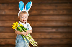 Happy laughing baby boy in bunny ears with  yellow tulips on  wo. Happy laughing baby boyin bunny ears with  bouquet of yellow tulips on wooden background Stock Photo