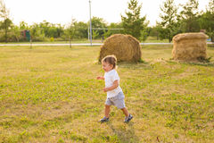Happy laughing baby boy running on summer or autumn field. Happy baby boy running on summer field Royalty Free Stock Images
