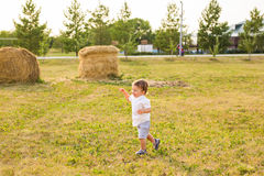 Happy laughing baby boy running on summer or autumn field. Happy baby boy running on summer field Royalty Free Stock Photo