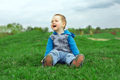 Happy laughing baby boy sitting on green field Royalty Free Stock Photography