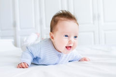 Happy laughing baby enjoying her tummy time. In a white nursery Stock Image