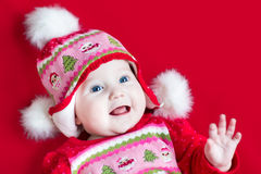 Happy laughing baby girl in Christmas knitted hat. Portrait of an adorable baby girl with beautiful blue eyes wearing a Christmas decorated knitted hat and Stock Photo