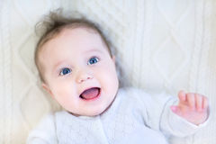 Happy laughing baby girl on knitted blanket. Happy laughing baby girl relaxing on a warm knitted blanket Royalty Free Stock Photos