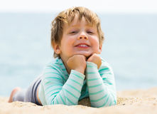 Happy laughing baby. Girl laying on sand Stock Photography