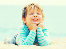 Happy laughing baby. Girl laying on sand Royalty Free Stock Photo