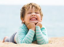 Happy laughing baby girl. Laying on sand beach Royalty Free Stock Image