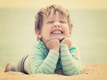 Happy laughing baby girl. Laying on sand beach Stock Photography