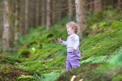 Happy laughing baby girl playing in pine forest Stock Photos