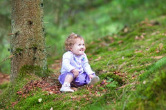 Happy laughing baby girl playing in pine wood forest Stock Photos
