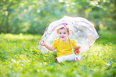 Happy laughing baby girl playing under umbrella Royalty Free Stock Photography