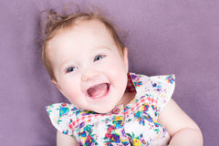 Happy laughing baby girl on purple background Royalty Free Stock Photography