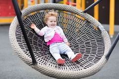 Happy laughing baby girl relaxing on a swing Royalty Free Stock Photo