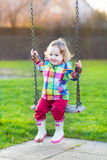 Happy laughing baby girl on swing in garden Royalty Free Stock Images