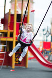 Happy laughing baby girl in a swing on a playground Royalty Free Stock Images