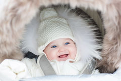 Happy laughing baby girl in a warm stroller Stock Photography